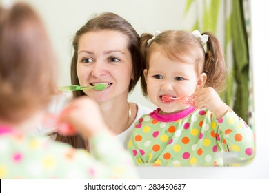 mom teaching daughter child teeth brushing in bathroom