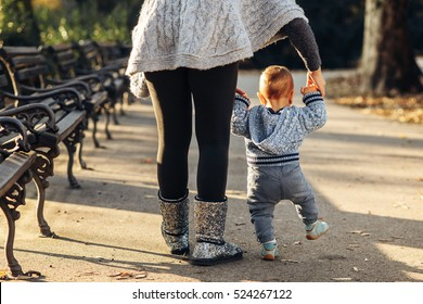 Mom teaching her son's first baby steps in the park