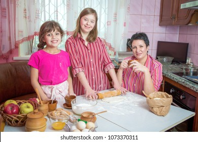 Mom teaching her two children cooking on the kitchen. Parent together with  youngest daughter and daughter with Down syndrome making pie and cookies. Family at home lifestyle photo.