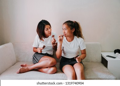 Mom and teenage daughter eating chocolate bar on sofa at home in living room, Happy family together.