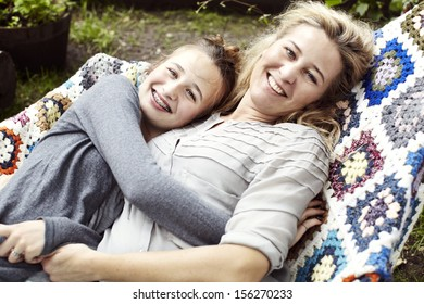 Mom and teenage daughter lying in a hammock