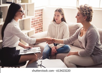 Mom and teenage daughter are visiting physiotherapist. Mother and doctor shaking hands