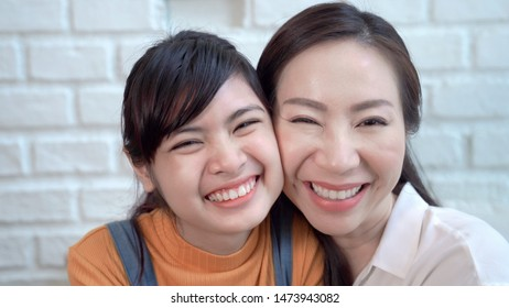 Mom and teenager daughter is having fun using video call to talk to father