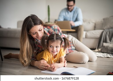 Mom is there to teach us everything. Family at home. Mother helping her daughter with homework. Focus on foreground.