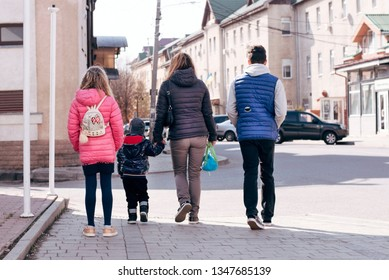Mom with three children goes from church to home on foot in the city. Rear view. The diversity of children between the ages is well visible