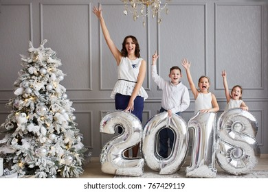 Mom and three children keep the numbers 2018. New Year's Eve