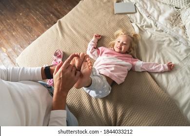 Mom tickles her little daughter's feet. The girl laughs merrily.