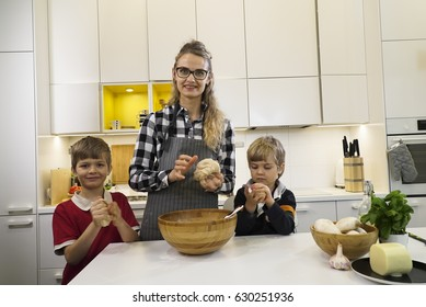 Mom and two children knead dough for pizza on the kitchen