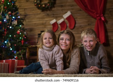 Mom with Two children lie on the floor near the Christmas tree, happy Christmas! Family with children meet at home christmas