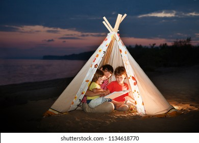 Mom and two children are reading a book with flashlights in tent in the evening on the river bank.