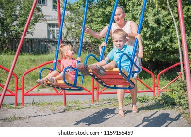 Mom with two children walking outdoor, warm weather. Lifestyle portrait mom and kids in happiness at the outside, vacation moments