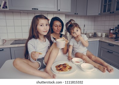 Mom and two daughters eat pancakes in the kitchen
