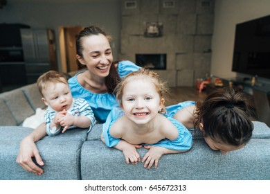 Mom, two daughters and a little son on the couch are having fun