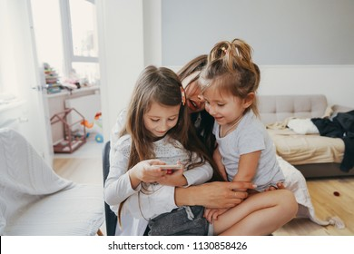 Mom and two daughters are looking for something in the smartphone