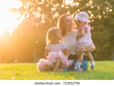 Mom with two daughters sitting in the park on the grass