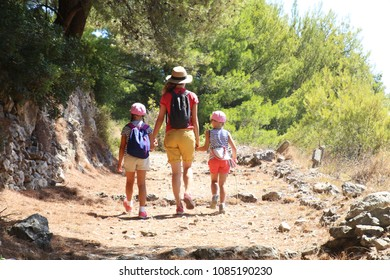 Mom with two daughters travels along a beautiful path in the mountains over the sea.