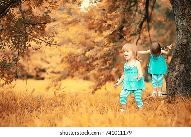 Mom with two daughters twins for a walk in the autumn park