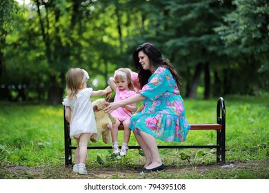 Mom with two daughters twins for a walk in the park