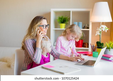 Mom with two daughters working from home