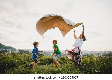 Mom and two her little sons throw up plaid on a green field in the rays of evening sun