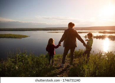 mom and two kids walk near the river. Social Distancing. end of a quarantine. Staycations, hyper-local travel,  family outing, getaway, natural environ