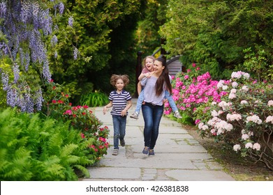 Mom with two kids walking along the alley blooming garden. Girl tired and mother carrying her on his shoulders. Boy walking near. Children enjoyed the walk. Walking in the fresh air for health