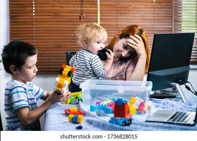 Mom with two little boys on his knees tries to laugh at home . A young woman looks after children and works on a computer. Mother does home business, soft focus
