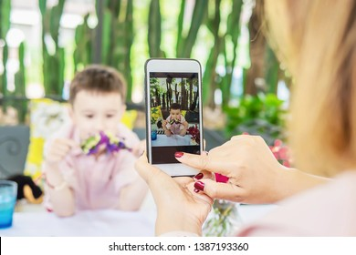 Mom use mobile phone take a photo of her son in restaurant - family lifestyle mother and son enjoy moment concept