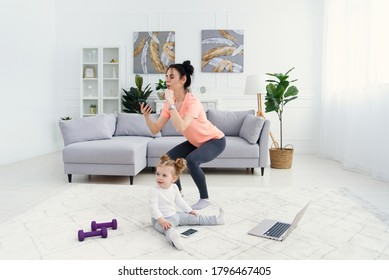 Mom uses smart phone while doing morning work-out at home. Mother does fitness exercises, healthy lifestyle concept.