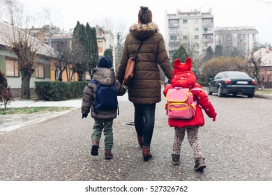 Mom walking down the street with children