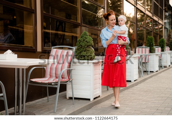 mom walks along the summer cafe and carries her daughter in her arms, they are stylishly dressed
