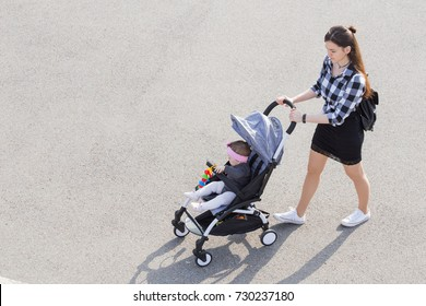 mom walks with a stroller. view from above