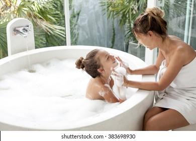 Mom washing her child in luxury hotel outdoor bath with a foam, still life