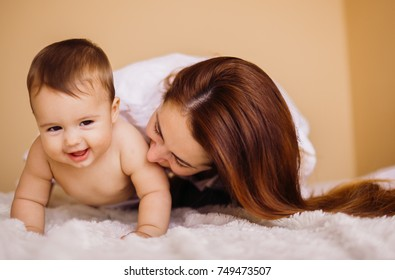 Mom in white shirt plays with little boy on white bed