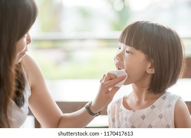 Mom wipes mouth for her child at cafe. Asian family outdoor lifestyle with natural light.