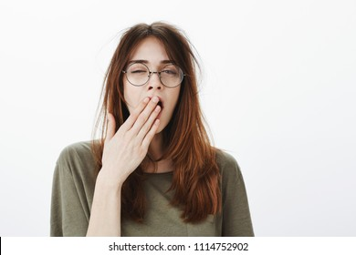 Mom woke up daughter very early. Shot of sleepy attractive caucasian woman with messy brown hair, wearing glasses, feeling tired after night without sleep, yawning, covering opened mouth with palm