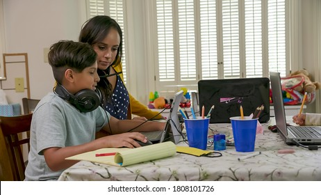 A mom working from home and sharing a small space with her children who are attending school via virtual classrooms stops to help her son. - Shutterstock ID 1808101726
