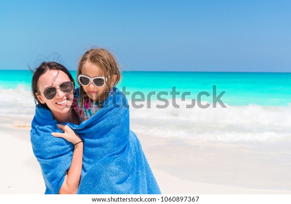 Mom wraps a small daughter with a towel after swimming in the sea