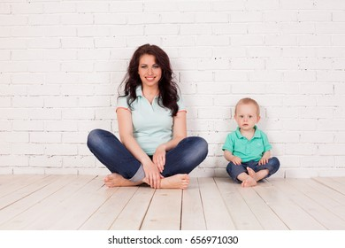 mom and young boy son sit on the floor white brick wall