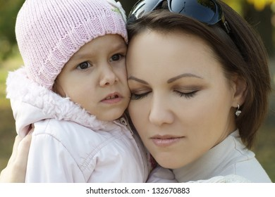 Mom and young daughter  walking in the park in autumn