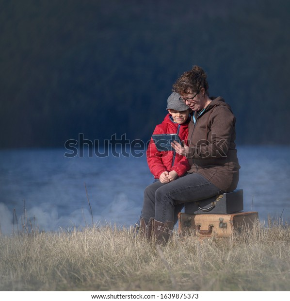 Mom and young son sitting on several retro suitcases looking at a tablet by the water.