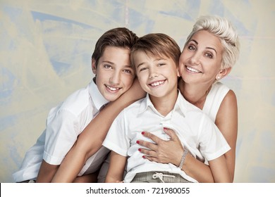 Mom with young sons posing, smiling to the camera.
