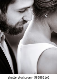 A moment before a kiss of bearded man to woman's neck