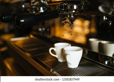 The moment of the brewing process of espresso. Coffee pours into two white cups.