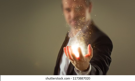 Moment of creation - Business man creating energy sparkles with his hand