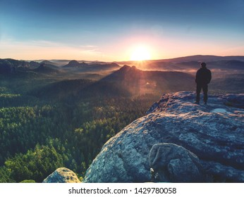 Moment of loneliness. Sportsman with hands in pockets stand on the rock peak and watching the sunset.