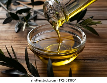 The moment olive oil is poured into a glass bowl set against a wooden background