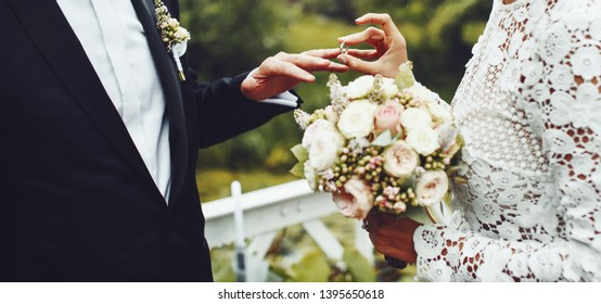 The moment of putting a wedding ring, bridal couple having their marriage ceremony.