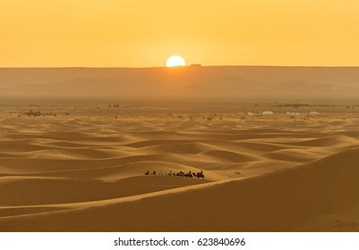 Moment of sunrise at Sahara Desert near Merzougha in Morocco with a small group of people riding camel on the sand dunes