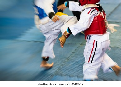 Moment of Taekwondo Kids in the stadiums. Athlete to strike an opponent during the tournament taekwondo kids. Add effect zoom for movement feeling.